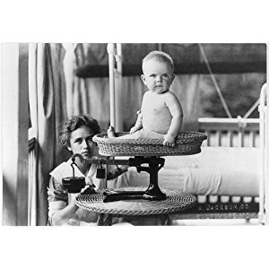 Photo: Baby being weighed by nurse on scale,c1912,baby boy